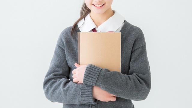 両手にノートを持つ女子高生