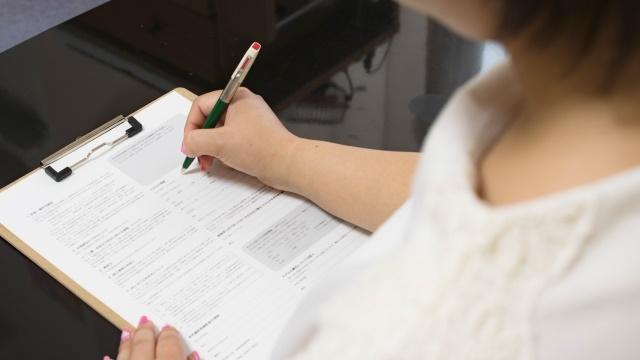 紙に書く女性
